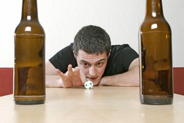 Junger Mann mit leeren Bierflaschen, kickt einen kleinen Fußball mit dem Finger