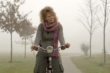 Frau auf dem Fahrrad im Herbst
