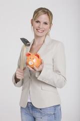 Frau jung mitSparschwein und Hammer