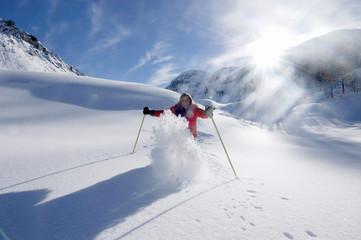 Österreich, Salzburger Land, Junge Frau beim Skifahren in den Bergen