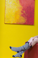 Beine einer Frau, Ringelstrümpfe, vor eigenem Gemälde