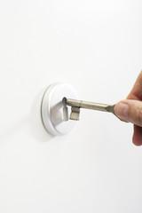 Hand führt Schlüssel in Schlüsselloch