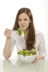 Junge Frau isst frischen Salat aus einer Schüssel