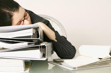 Erwachsene Frau mittleren Alters schläft bei der Arbeit