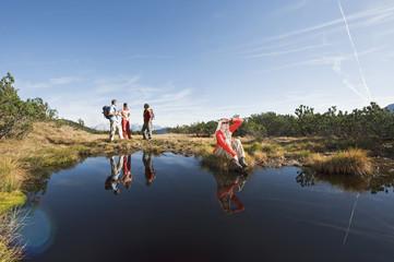 Österreich, Salzburger Land, Vier Wanderer in der Nähe eines Sees