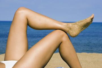 Frau liegt am Strand mit den Füßen oben