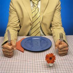 Mann sitzt am Tisch mit leerem Teller vor sich
