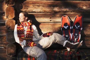 Frau mit Schneeschuhen sitzt vor Hütte