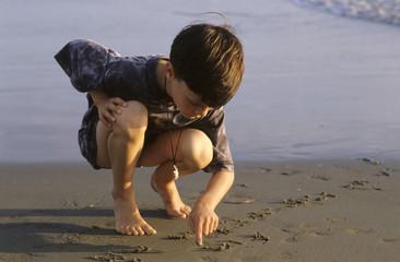Junge, Kind schreibt in den Sand