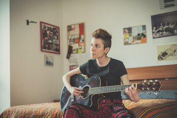 young lesbian stylish hair style woman playing guitar