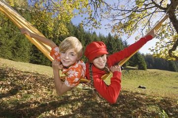 Österreich, liegend Salzburger Land, Altenmarkt, Junge und Mädchen in der Hängematte