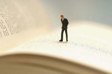 Figur eines Geschäftsmannes auf Buch