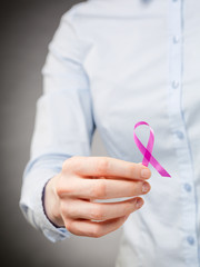Female Hand Holding a Pink Ribbon