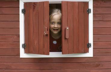 Mädchen schaut durch ein Fenster, lächelnd
