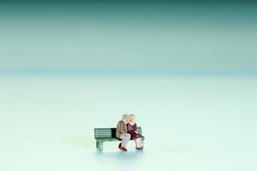 Figuren, ein Paar, sitzen auf der Bank