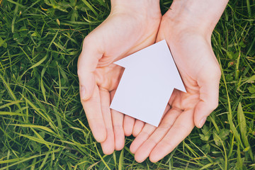 Hands Holding Family House on Grass