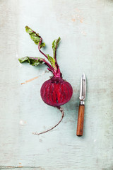 Ripe beet with leaves on textured background