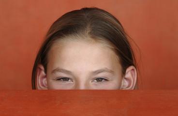 Mädchen schaut kess über eine Tischkante