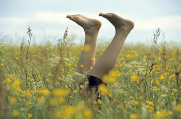 Frauenfüße schauen aus hohem Gras