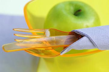 Plastikbesteck, Plastikschüssel und grüner Apfel