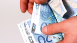 Hand counting wad of twenty euro notes