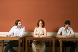 Zwei junge Männer und eine Frau bei schriftlichem Test, einer spickt, guckt ab