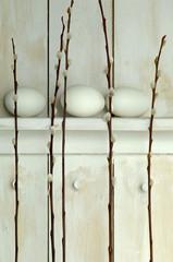 Ostereier auf Regal mit Weidenkätzchen Zweigen