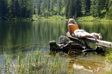 Junge Frau liegt auf Holzbrett am See