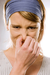 Junge Frau, hält sich die Nade zu, es stinkt