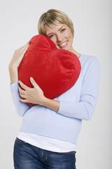 Frau jung mit herzförmigen Kissen, Lächeln, Portrait