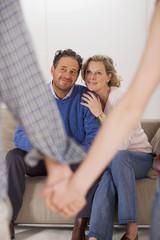 Teenager-Paar Händchen haltend, sitzen die Eltern auf dem Sofa
