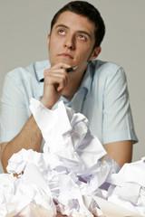 Junger Mann sitzt am Schreibtisch mit zerknittertem Papier