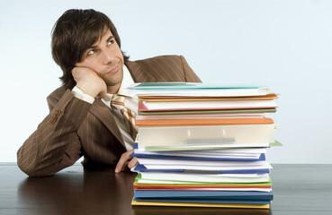 Geschäftsmann sitzen am Schreibtisch mit Haufen von Dateien, Wegschauen