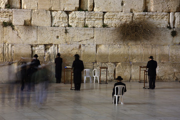 People praying at  Western/Wailing wall at night.