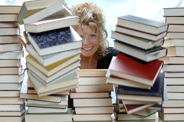 Frau schiebt Stapel Bücher, Lächeln