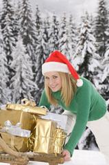 Österreich, Salzburger Land, Altenmarkt, junge Frau schiebt Schlitten voller Weihnachtsgeschenke