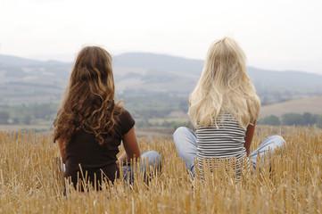Mädchen sitzt im Maisfeld, Rückansicht