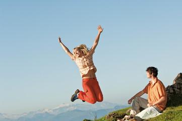 Mann sitzt, Frau springt in die Luft, beim Wandern