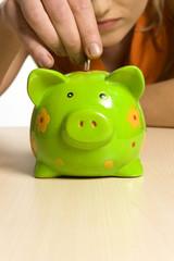 Junge Frau mit grünem Sparschwein