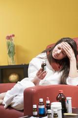 Frau sitzt im Stuhl, Erkältung, mit Medizin