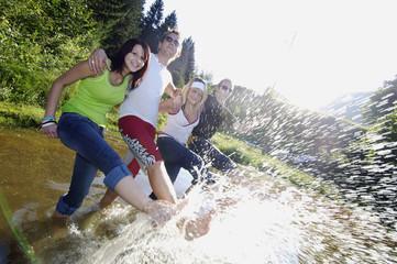 Vier junge Leute albern im Fluss herum