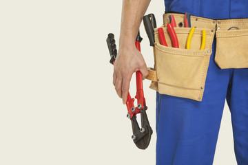 Mann tragen Werkzeuggürtel halten Zangen, close-up