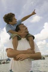 Vater trägt Jungen auf den Schultern, lächelt