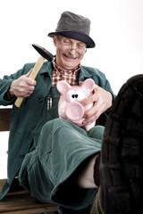 Mann schlachtet Sparschwein, lächelnd