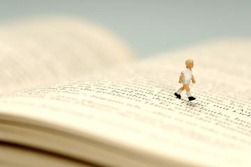 Figur eines Kindes läuft über Buch