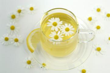 Kamillentee in der Tasse mit Blumen und Zitrone, close-up