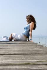 Junge Frau sitzt auf Steg, Seitenansicht