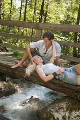 Österreich, Steiermark, Paar ruht aus, auf hölzerner Brücke über Bach