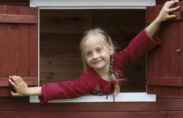 Mädchen lehnt aus dem Fenster