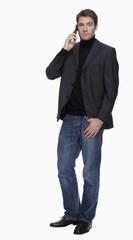 Junger Mann in Jeans und Jacke, telefonierend